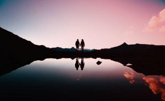 Coppia tenersi per mano davanti al lago Grevasalvas nei Grigioni in Svizzera - Trovare l'amore in Svizzera