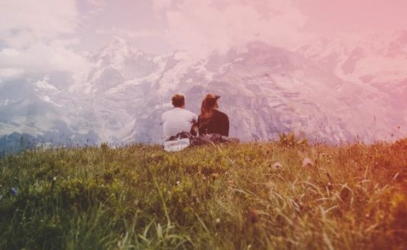 Couple in love on grass facing mountains inLauterbrunnen, Switzerland